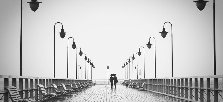 How to make a relationship last depicted by a Couple with lasting love walking down boardwalk